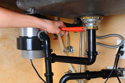 Plumber repairing a customers garburator in vancouver