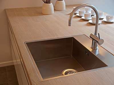 Stainless steel kitchen sink installation done by DJ Plumbing.